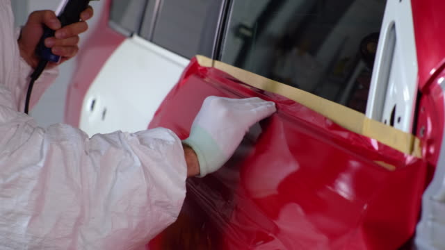 Applying red car vinyl wrap using heat gun - vídeo