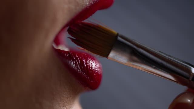 vidéos et rushes de appliquer du rouge à lèvres rouge sur les lèvres d'une femme avec une brosse à maquillage. maquillage. - rouge à lèvres rouge