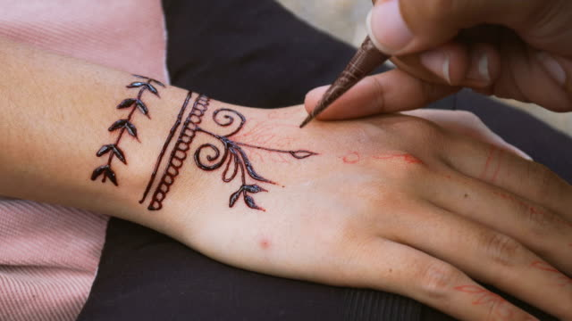 vídeos de stock e filmes b-roll de applying simple henna paint onto back of hand - mandala