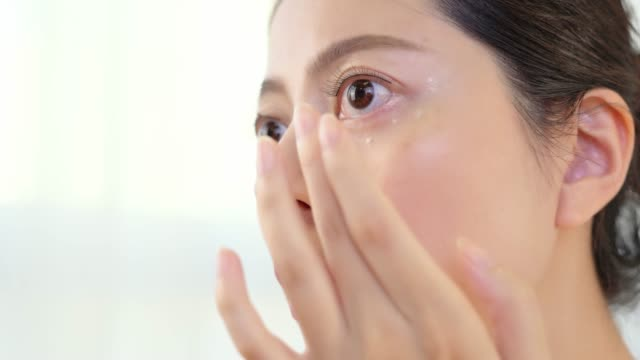 applying skin cream under eyes. video