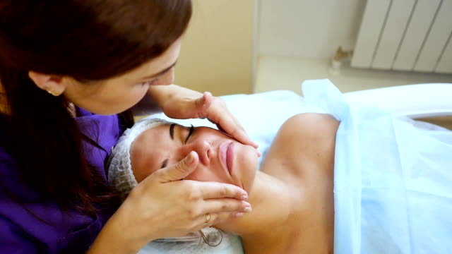 Applying the cream on the face. Mechanical cleaning of the face. Cosmetology. video