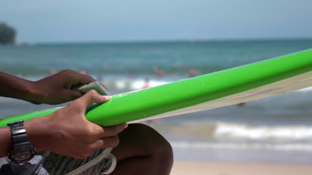 Applying wax on a surfboard video