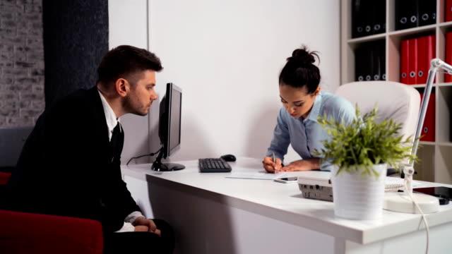 vidéos et rushes de rendez-vous entre une femme et un homme d'affaires au bureau - notaire