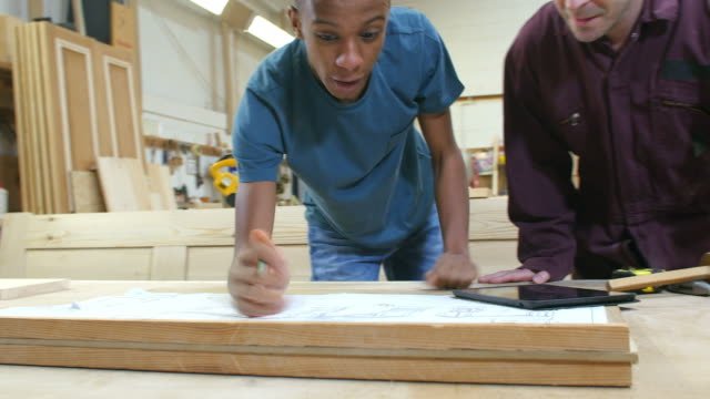 Apprentice looking at plans in workshop is joined by carpenter - they look at digital tablet together video