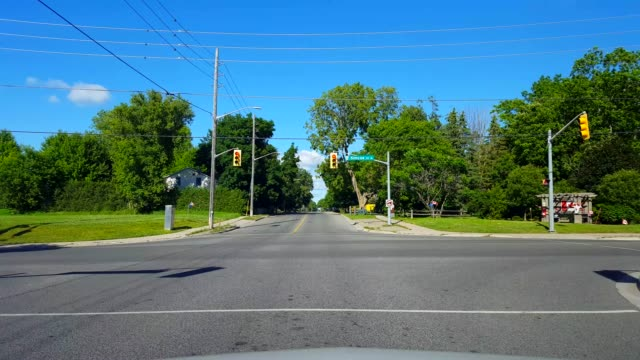 Approaching Canadian City Intersection Road Traffic During Day.  Driver Point of View POV of Canada Town Life Cityscape With Cars Driving By Canadian Flags Approaching Canadian City Intersection Road Traffic During Day.  Driver Point of View POV of Canada Town Life Cityscape With Cars Driving By Canadian Flags canada day videos stock videos & royalty-free footage