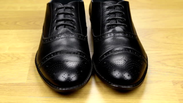 Approaching, pair of black classic men's shoes standing on a wooden floor.