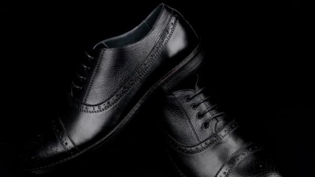 Approche, paire de chaussures noires classiques pour hommes debout sur un fond noir. La mode masculine. - Vidéo