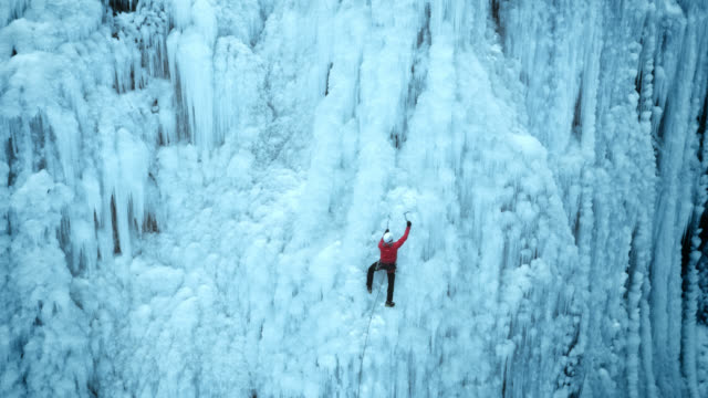approaching the ice climber in the steep slope - extremsport stock-videos und b-roll-filmmaterial