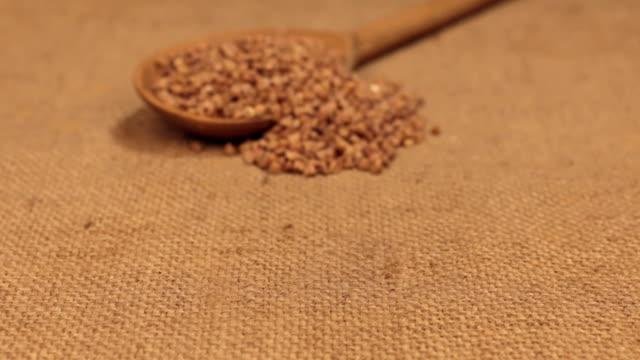 Approximation of a wooden spoon overflowing with buckwheat grains, lying on burlap video