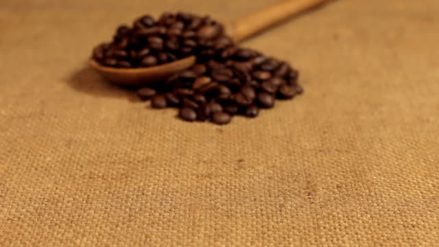 Approximation of a wooden spoon overflowing with coffee beans, lying on burlap video