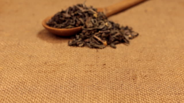 Approximation of a wooden spoon overflowing with dried green tea leaves, lying on burlap video