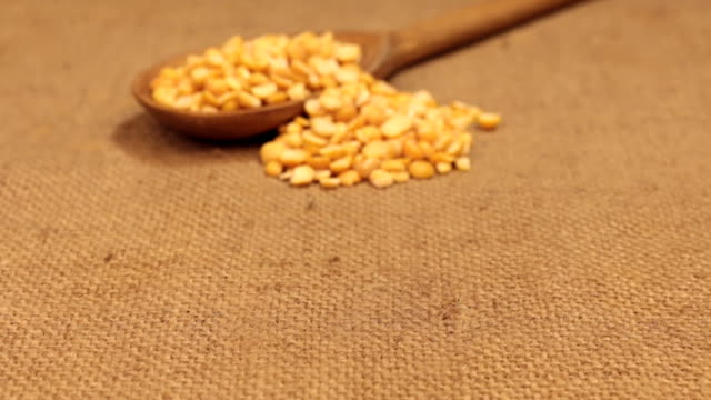 Approximation of a wooden spoon overflowing with dry peas grains, lying on burlap video