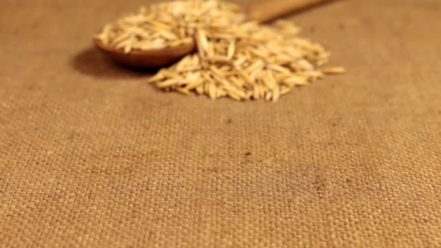 Approximation of a wooden spoon overflowing with oat grains, lying on burlap video