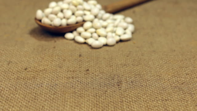 Approximation of a wooden spoon overflowing with white beans, lying on burlap video