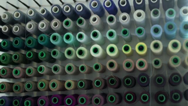 annäherung an bunte rollen aus wollfaden hängen an einem wandhintergrund - kurzwaren stock-videos und b-roll-filmmaterial