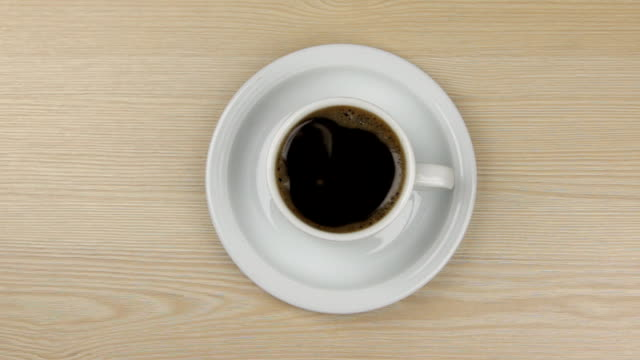 Approximation of hot steaming cup of coffee standing on a wooden table video