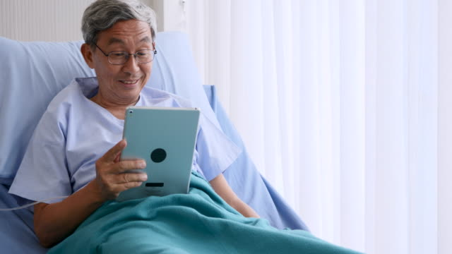 appy elderly patient sitting on bed and making video call with tablet at hospital video