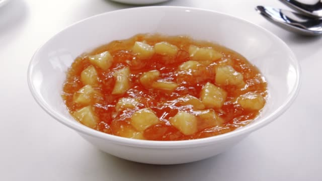 Apricot jam with slices of fresh ripe fruit. video