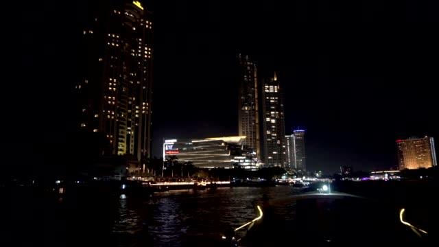 nisan, 2019 - bangkok, tayland - chao phraya nehri. işıklı dükkanlar, alışveriş merkezleri ve restoranlar arasında nehir üzerinde gece bir tekne de yelken. - stupa stok videoları ve detay görüntü çekimi