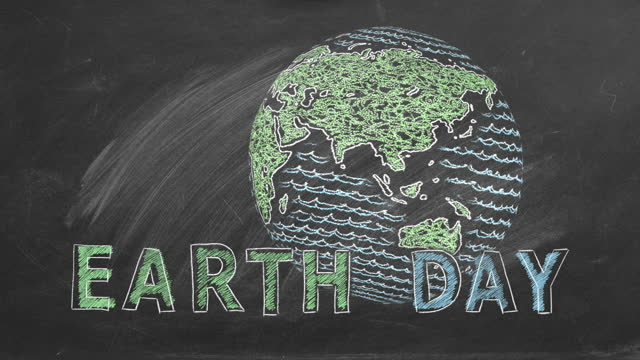 22 April. Concept of Earth day Rotating world with lettering EARTH DAY hand drawn in chalk on a school blackboard. earth day stock videos & royalty-free footage