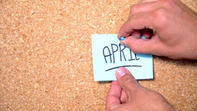 april word on paper pinning up on corkboard by a man - april fools day stock videos and b-roll footage
