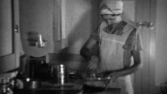 1936: Aproned women cooking in kitchen sifting flour for biscuits. video