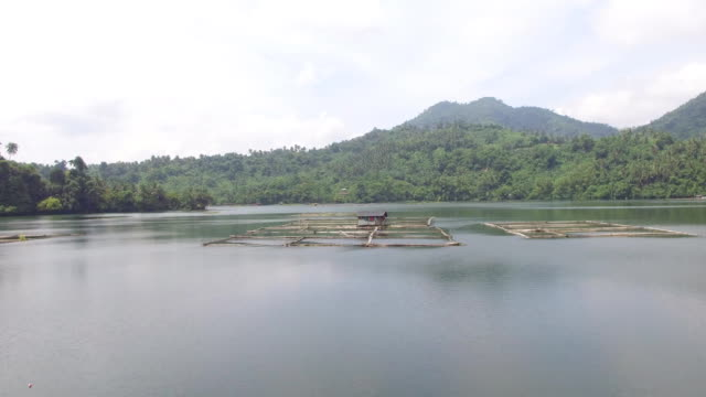 Aquaculture harnessing Mojicap lake potential to sustain livelihood of lake dwellers. Shanty and bamboo structures built in the middle of the lake. Drone aerial shot video