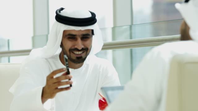 Arab business people wearing national dress wireless technology video
