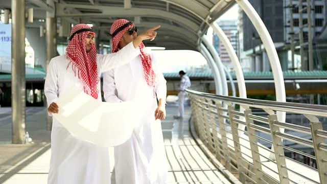 arab businessman and builder. low angle view of arab businessman and builder with blueprint looking away - arabia saudita video stock e b–roll
