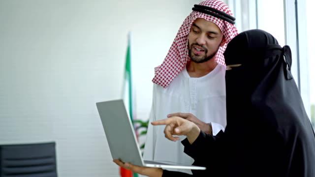 stockvideo's en b-roll-footage met arabische zakenman en onderneemster die een laptopcomputer gebruiken die bij het bureau werkt - perzische golfstaten