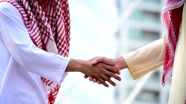 Arab Businessman shaking hands together. Teamwork business partner wear Muslim dress Shake Hands with Partnership Concept. Success UAE diversity people trust make commitment by handshake