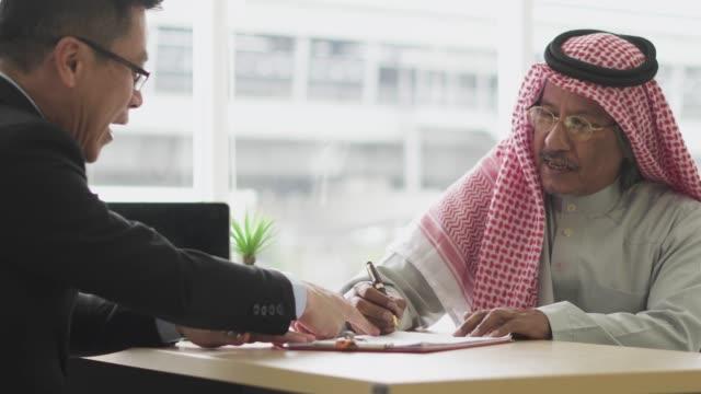 Arab businessman signing partnership agreement
