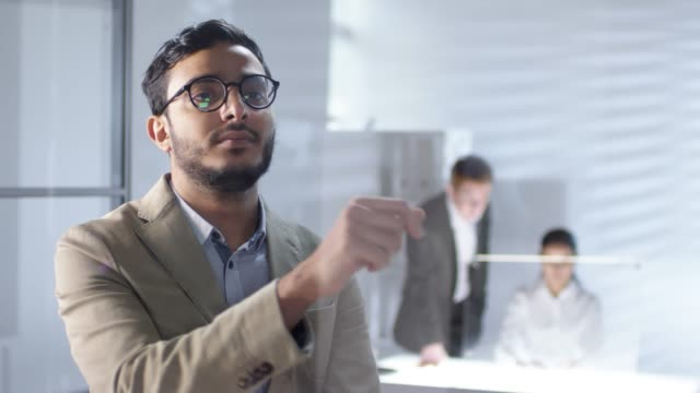 Arab Businessman Using Invisible Multi-Touch Screen on Glass Wall in Office Handsome middle eastern businessman in eyeglasses swiping and tapping on invisible multi-touch screen on glass wall in office while colleagues working in background. Suitable for adding AR graphics tapping stock videos & royalty-free footage