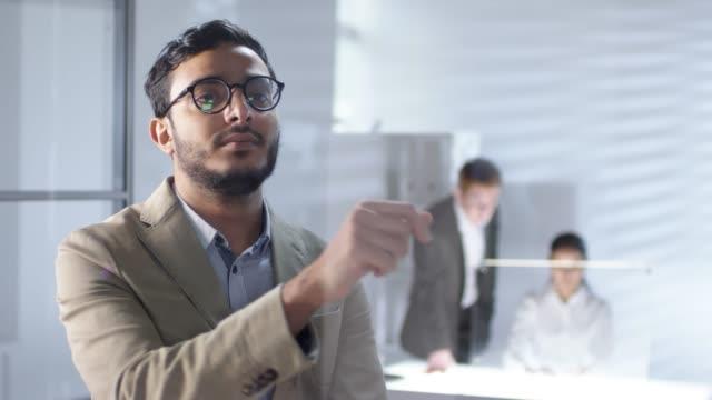 arab businessman using invisible multi-touch screen on glass wall in office - picchiettare video stock e b–roll