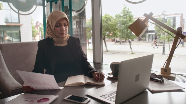 Arab businesswoman doing research in cafe video