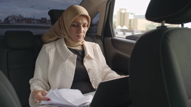 Arab businesswoman working in back seat of car video