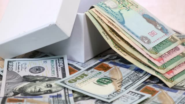 Arab Currency Dirhams in White Gift Box on a Background of American Dollars Bank notes on Rotating Table. Global Business Concept.