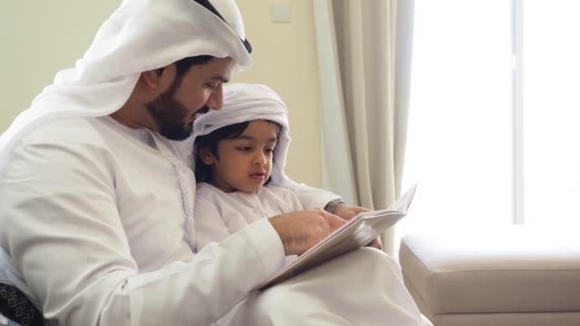 vídeos y material grabado en eventos de stock de dad árabe e hijo leyendo un libro para la tarea en casa - islam