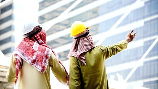 ingegnere arabo consultare progetto di costruzione insieme tenere progetto, indicando in cantiere serio problema moderna città musulmana degli emirati arabi uniti. diversità multiculturale uomini d'affari incontro parlando - quality video stock e b–roll