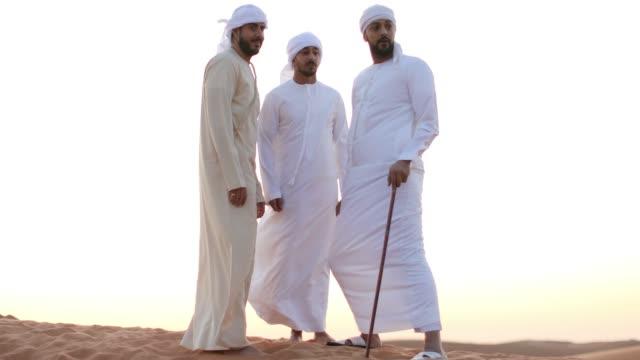 arab friends having casual conversation during their desert visit - cultura del medio oriente video stock e b–roll