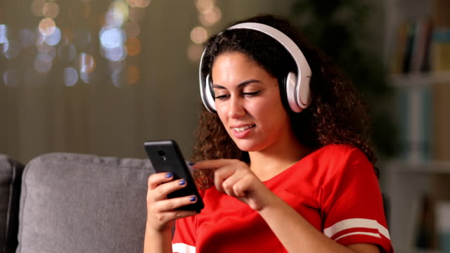 arab girl listening to music checking phone at home - cuffie wireless video stock e b–roll
