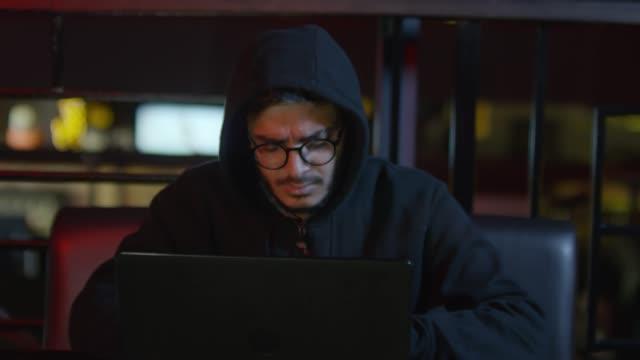 arab hooded hacker coding - conspiracy стоковые видео и кадры b-roll