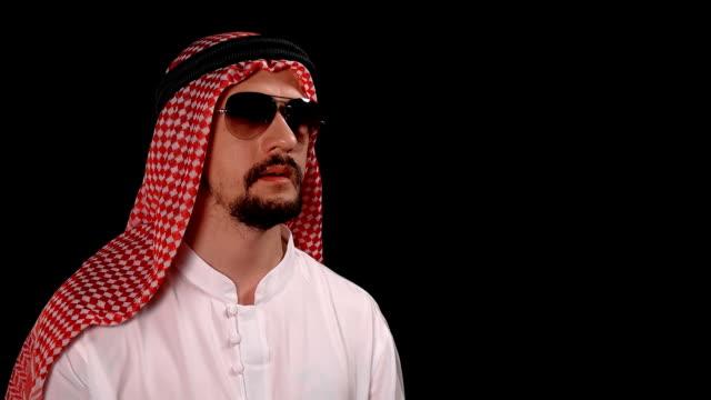 stockvideo's en b-roll-footage met arabische in klederdracht werpt een blad met de inscriptie van het land noord-korea - kampioenschap