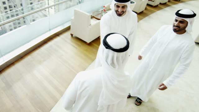 Arab males in national dress handshake greeting downtown video