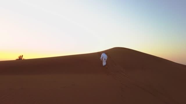Arab Man Climbing the Sand Dunes