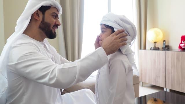 arab man fixing keffiyeh to his son - arab стоковые видео и кадры b-roll
