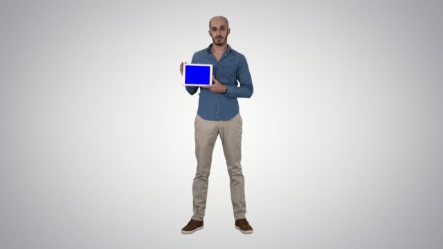 Arab man showing blank tablet screen on gradient background