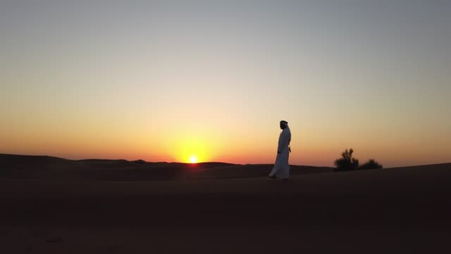 Arab Man Strolling on the Sand Dunes During Sunset