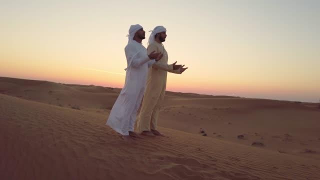 vídeos y material grabado en eventos de stock de hombres árabes orando juntos en el desierto - islam