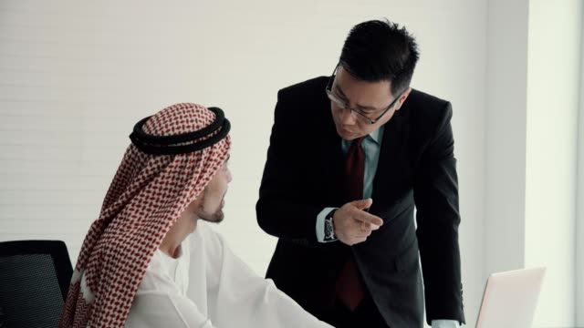 arab middle east businessman having meeting with an asian businessman - cultura del medio oriente video stock e b–roll
